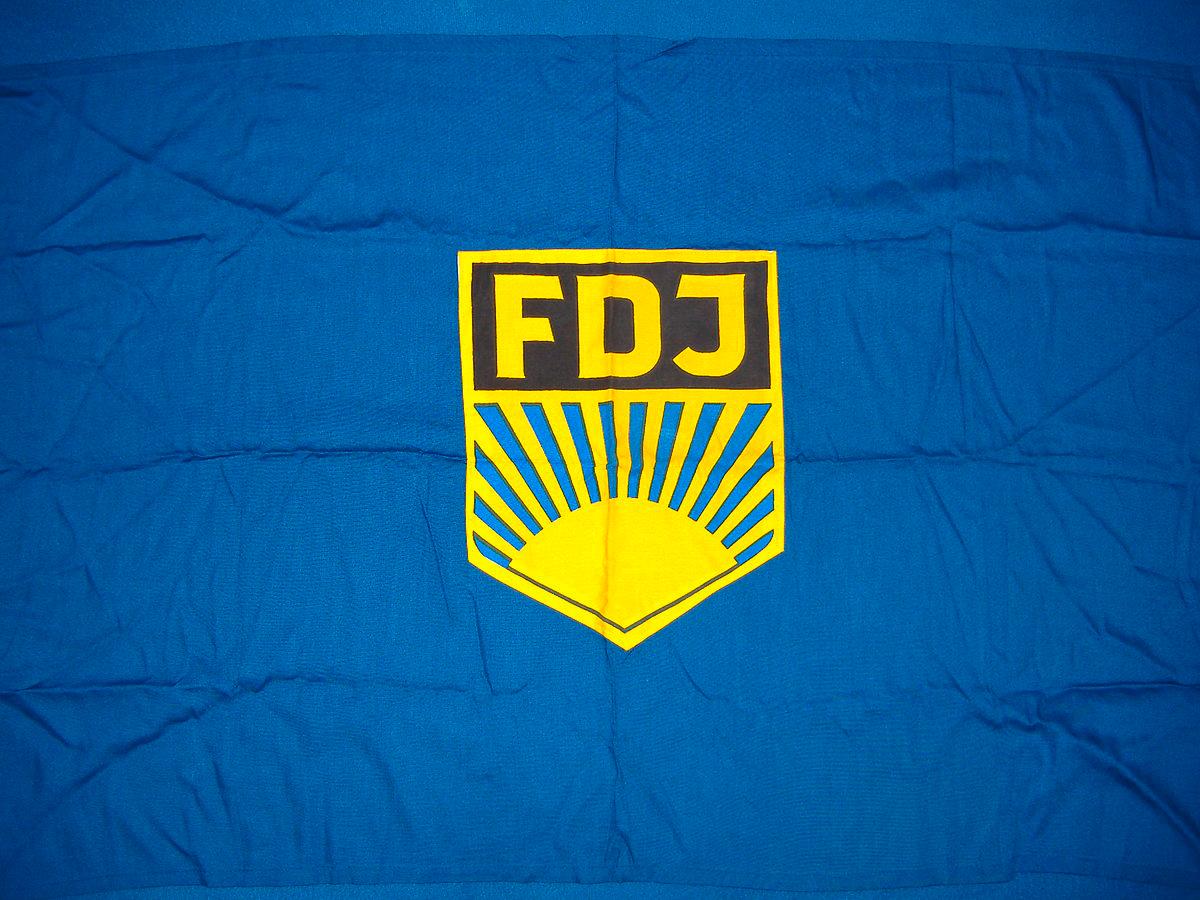 Die Fahne der Freien Deutschen Jugend (FDJ) in der ehemaligen DDR zeigt einen gelben Schriftzug des Akronyms FDJ auf einem blauen Hintergrund.