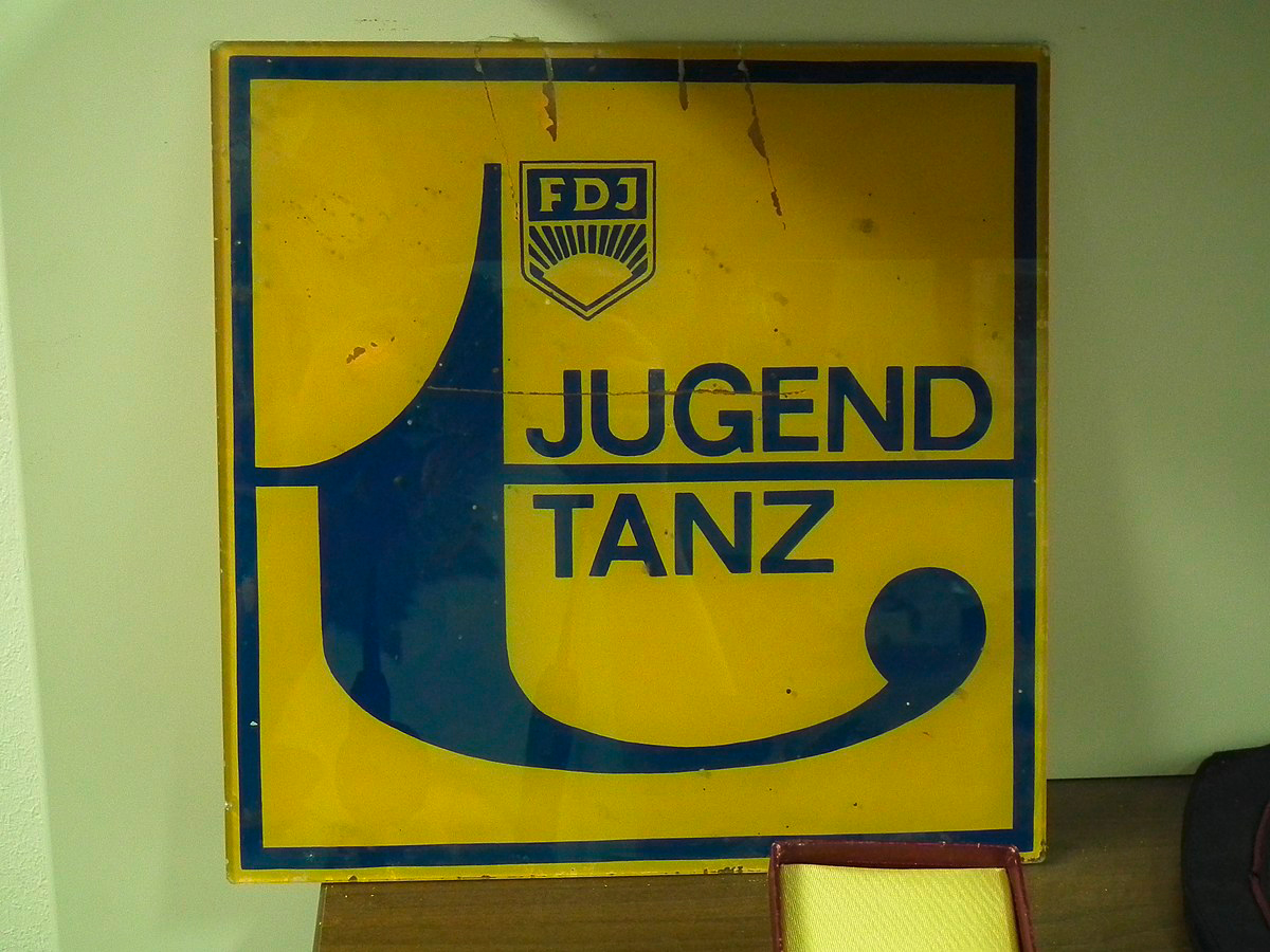 """Das gelbe Schild mit blauem Schriftzug """"Jugendtanz"""" zeigt ein Werbeplakat der FDJ von Discoveranstaltungen und anderen Tanzvergnügen."""