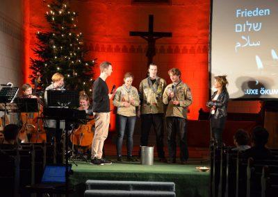 """Die Pfadfinder der DPSG-Stamm Tilia überbringen das Friedenslicht in der Jugendkirche PAX in Leipzig. Gemeinsam stehen sie vor dem großen Kreuz. Im Hintergrund sind Musiker*innen und das große Wort """"Frieden"""" zu sehen."""