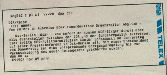 Zu sehen ist eine Eilmeldung der Deutschen Presseagentur vom 09.11.1989. In dieser wird die Begründung von Reisegesuchen aufgehoben, die der Politiker Günter Schabowski in Ost-Berlin bekannt gegeben hat. Kurz darauf folgt die Öffnung der Mauer, indem bekannt gegeben wurde, dass fortan keine Gründe mehr zur Reiseerlaubnis angegeben werden müssen.