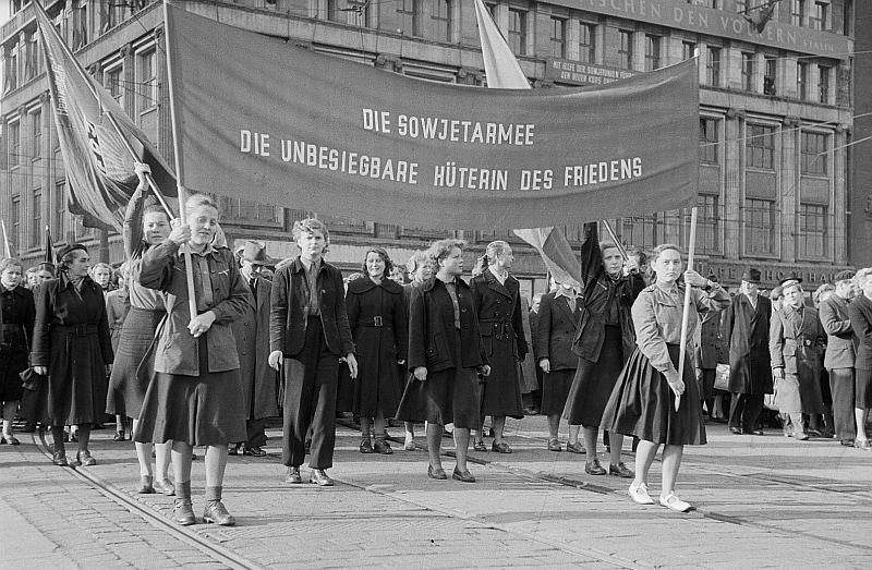 """Auf dem Bild sind Mitglieder der Freien Deutschen Jugend zu sehen, die auf dem Leipziger Karl-Marx-Platz anlässlich des Jahrestages der Oktoberrevolution demonstrieren. Vier Frauen halten eine große Fahne mit dem Schriftzug """"Die Sowjetarmee – Die unbesiegbare Hüterin des Friedens"""" nach oben."""