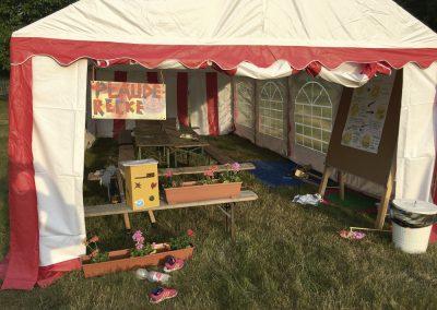 Die Plauderecke auf dem Kidscamp der Falken ist ein großes Zelt, geschmückt mit Blumen, einem Kummerkasten und verschiedenen Sitzmöglichkeiten.