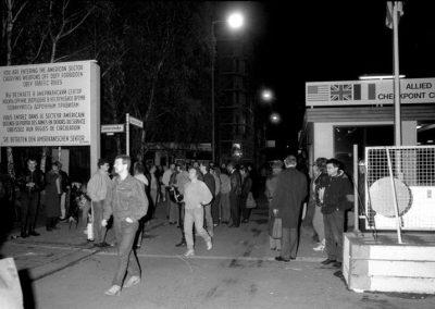 """Das Bild zeigt eine Menschenmenge am Grenzübergang """"Checkpoint Charlie"""" in der Nacht des Mauerfalls."""