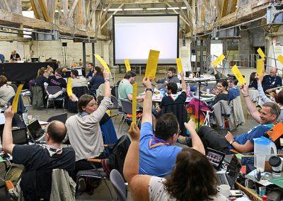 Das Bild zeigt viele Mitglieder der Deutschen Pfadfinderschaft Sankt Georg bei einer Abstimmung ihrer Bundesversammlung.
