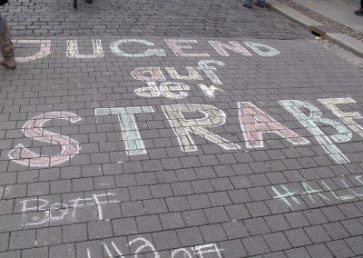 """Auf die Pflastersteine am Nikolaikirchhof wurde """"Jugend auf der Straße"""" mit Kreide geschrieben und weist vor Ort auf die Protestaktion hin."""