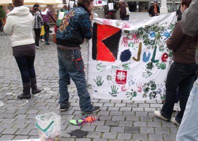 Zwei Jugendliche halten ein Transparent der Kolpingjugend, auf dem viele Handabdrücke, das Caritas-Logo und der Schriftzug Kojule abgebildet sind.