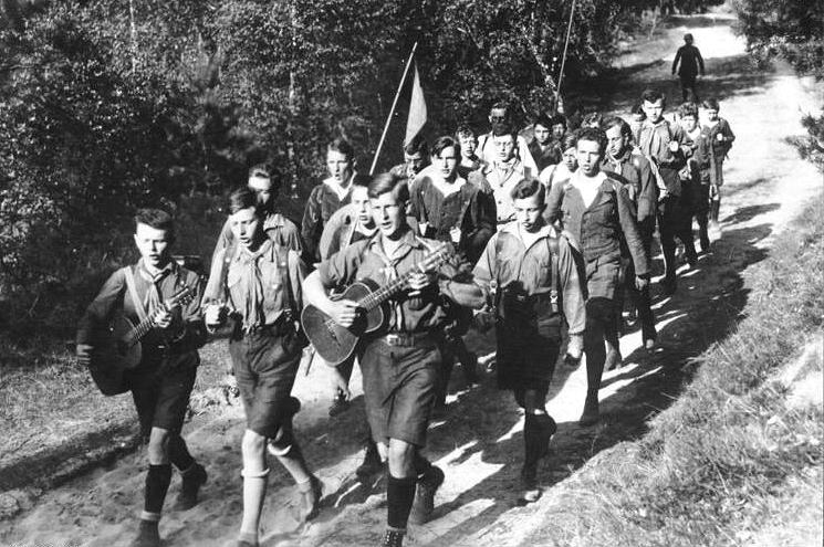 Das schwarz-weiße Bild zeigt eine Gruppe des Steglitzer Wandervogels aus Berlin auf großer Fahrt um 1930. Mehr als zwanzig junge Menschen ziehen mit Wanderkluft, Gitarre und Fahnen einen Wanderweg entlang.
